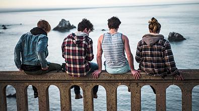4 jeunes sur un rebord face à la mer